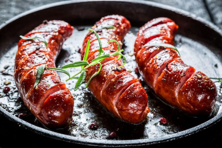 37305466 – grilled sausage with fresh rosemary on hot barbecue dish